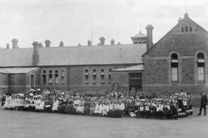 View taken in the yard at the back of Kapunda Primary School, with the children posing for the photographer. A number of teachers are also included. It appears to be a special occasion - there is a large wreath, a number of boys in uniform (two holding rifles), several of the children are holding posters, and all appear to be wearing their Sunday best. DATEca.1900